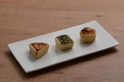 Auf dem Foto sind die drei verschiedenen Mini-Quiche-Sorten des Herstellers Maitre Pierre zu erkennen. Sie sind auf einem länglich quadratischem wieißen Teller auf einem Holzfußboden. Links befindet sich ein dreieckiges Stück, in der Mitte ein quadratisches und rechts eine runde Mini-Quiche.