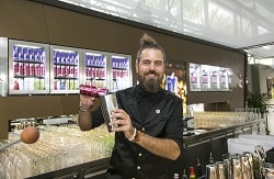 Man erkennt einen jungen Mann im schwarzen Hemd, der hinter einer Bar steht. Er ist Barkeeper, welches sich an dem Cocktailshaker und der Dose Energiedrink von der Marke Red Bull vermuten lässt. Er hat seine langen braunen Haare zu seinem Dutt gebunden und hat einen Vollbart. Im Hintergrund erkennt man in den Barvitrinen weitere Dosen Red Bull.