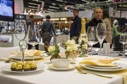 Auf dem Foto erkennt man einen gedeckten Tisch. Auf einer weißen Tischdecken befinden sich vier Teller mit dazugehörigem Besteck, Weingläser und gelbe Servietten. Die Servietten liegen jeweils auf den drei Tellern drauf. In der Mitte des Tisches ist eine gelbe Blume, eine Flasche Sekt und eine Schale zu sehen. Auf dem linken Teller liegen außerdem noch Süßigkeiten der Marke Ferrero auf dem Teller. Es sind Ferrero Rocher.