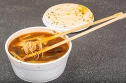 Auf dem Foto erkennt man eine weiße Plastikschale, die mit Nudelsuppe gefüllt ist. Die Suppe hat eine rot-bräunliche Farbe. Die Nudeln werden mit Hilfe der auf der Schale liegenden Essstäbchen gehalten. Im Hintergrund erkennt man den dazugehörigen Deckel.