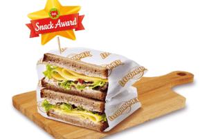 """Auf dem Bild ist ein mit Schinken und Käse belegtes Sandwich zu erkennen. Beide Teile des Sandwiches liegen übereinander und sind jeweils in eine weiße Papierverpackung verkleidet. In dem Sandwich-Turm steckt ein Fähnchen von der Bel Groupe. Auf dem goldenen Stern mit rotem Band steht """"Snack-Award"""" geschrieben. Die Bel Groupe hat nämlich dieses Jahr wieder den Snack-Award vergeben."""