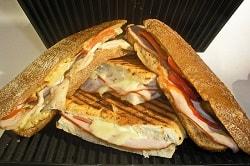 Auf dem Foto erkennt man vier Sandwiches, die übereinander gestapelt sind. Sie befinden sich in einem Grill, dies erkennt man an den schwarzen Rillen oben und unten. Außerdem sind die Sandwiches gegrillt worden. Der Käse ist zerschmolzen und sie sind noch mit Salami, Schinken und Tomate gefüllt.
