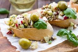 Veggie und vegan_auf dem Bild sind zwei gefüllte backwaren zu sehen. Die Füllung besteht aus oliven, käse, geraspelten Radischen und Basilikum.