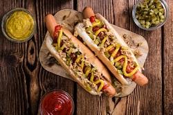Hot Snacks_auf dem Bild sind zwei riesen hot dogs zu sehen, die von oben fotografiert wurden. beide liegen auf einem Brett und haben als topping eine Senf spur.