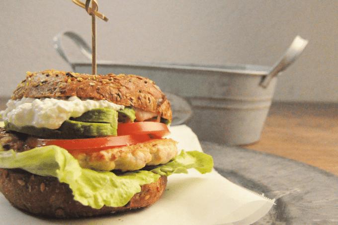 Auf dem Foto ist ein Burger zu erkennen. Die Burger Buns sind dabei aus dem proteinreichem Teig von Point of Food. Zwischen den Buns befindet sich Salt, ein Stück Hähnchen, Tomate und Gurke. Der Burger ist auf einer Serviette.