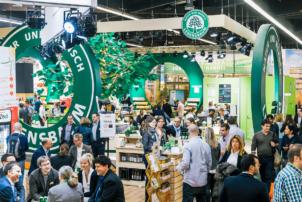 Auf dem Bild sind Aussteller der Leitmesse für Bio-Lebensmittel, der Biofach, zu sehen. Große grüne Runde Kreise dekorieren den Raum.