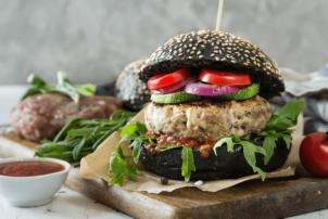 Ein schwarzes Burgerbrötchen beinhaltet ein Patty aus Fleisch, Rucola als Salat, Ketschup als Soße und oberhalb des pattys sind Zucchini, Zwiebeln und Tomaten. Der Burger ist auf einem Stück Papier auf einem Schneidebrett. Rechts davon befindet sich eine Tomate.
