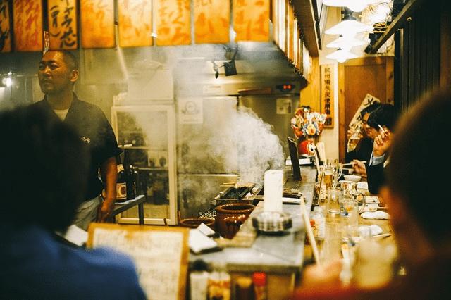 Food Impact_Delasia_Auf dem Bild ist ein kleiner asiatischer Imbisstand zu sehen, um dem wie an einer Bar leute drum sitzen und essen. Hinter dem tresen Bereich steht ein asiatischer Mann welcher am Kochen ist.