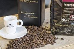 Auf dem Foto erkennt man eine Espresso-Tasse mit Untertasse und ausgestreuhte Kaffeebohnen rechts von der Tasse. Außerdem befinden sich jeweils rechts und dahinter eine Packung Espressobohnen auf dem Holztisch.