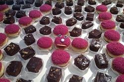 Auf dem Foto sind man Schokoladendesserts und pinke Berliner auf einem weißen Tisch auf der Messe Intergastra stehen. In der Mitte sind fünf Berliner angeordent, von denen der in der Mitte ein Gesicht besitzt, mit großen Kulleraugen, einem Mentos als Nase und einer hellen Linie aus Zucker als Mund. Die Berliner und Schokoladentörtchen drum herum sind für den to go Verzehr geeignet.