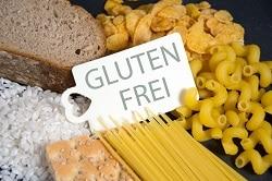 Auf dem Bild sind Nudeln, Brot, Cornflakes und grobes Salz um ein mittig platziertes Schild auf dem glutenfrei steht, angerichtet.