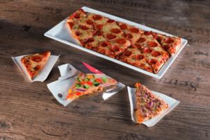 Auf dem Foto ist die GN Pizza von Point of Food abgebildet, sie in zwölf gleich große Dreiecke geteilt wird. Die GN Pizza ist auf einem weißen Teller und ist mit Salami belegt. Vor ihr sind drei Ecken auf Pappslices. Eine davon ist mit Salami belegt, die in der Mitts ist die Pizza Verdura, welche mit verschiedenen Arten Gemüse belegt ist, und der ganz rechte Point Snack ist die Thunfisch-Pizza von Point of Food. Alle Pizzen befinden sich auf einem Holztisch.