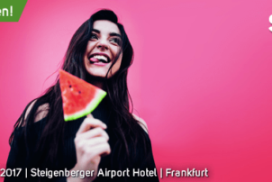 Auf dem Bild erkennt das man Logo des snack-Kongresses von 2017. Der Hintergrund ist pink und relativ mittig im Bild steht ein Mädchen mit einem schwarzen Pullover und hält ein Stück Wassermelone am Stiel. Sie lacht und streckt ihre Zunge raus.