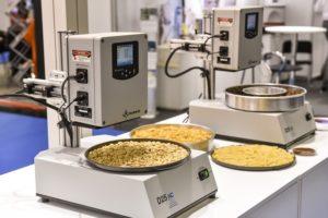 Auf dem Foto sind zwei Maschinen zu erkennen, die auf runde Bleche, die aussehen wie Pizzableche, Zutaten streuen oder verteilen. Die Maschinen befinden sich auf der Messe Anuga FoodTec.