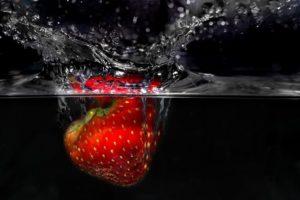 Auf dem Foto ist eine Erdbeere zu erkennen, die gerade in klares Wasser hineinfällt. Das Wasser spritzt.