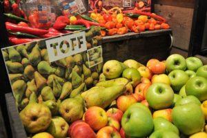 Auf dem Foto erkennt man im Vordergrund eine Variation an Äpfel und Birnen auf der Fruit Logistica beim Aussteller Toff. Im Hintergrund ist ebenfalls eine Ablage mit Gemüsevariationen,