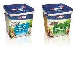 Homann Salatdressing- Verpackungen von den Sorten: Joghurt Kräuter und Kräuter Dressing. Beide stehen nebeneinander auf hellem Hintergrund und Spiegln sich vorne im Bild
