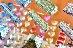 ISM 2018. Auf dme Bild sind eingepackte Schokoladenriegel in bunten farben zu sehen, welche auf einer Glasplatte liegen. Unter der oberen Gladplatte liegen weitere Süßigkeiten von dem Austeller ASTIR der ISM 2017.