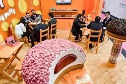ISM 2018. Auf dem Bild ist ein Messe-Stand der ISM 2017 abgebildet, auf dem ein riesieger abgebissener Donut zu sehen ist, mit rosa Streuseln und einer dunklen Creme-Füllung. Im Hintergrund sitzen Menschen an Runden Tischen und unterhalten sich.