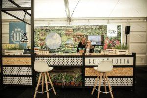 Auf dem Foto ist ein Aussteller auf dem internationalen Foodservice Forum, welches Rahmenprogramm der Internorga ist, zu sehen. Der Aussteller ist Foodtopia. Vor dem Stand stehen zwei weiße Barhocker. Der Stand ist verziert. Im Hintergrund erkennt man ein Bild mit einem Wald drauf, vor dem zwei Frauen stehen.