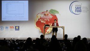 Auf dem Foto ist die Bühne des SAVE FOOD Kongresses abgebildet. Auf der Bühne steht ein Redner und referiert. Vor der Bühne sitzen Zuhörer, die jedoch nicht zu erkennen sind.