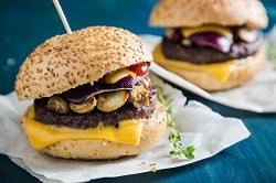 Ein Burger auf einem weißen Teller in einem Sesambrötchen und mit einem Hoszspieß fixiert. Er ist belegt mit schmelzenden Käse, einem Beef Burger Pattie, gebratenen Champignions und etwas Salat. Im Hintergrund ist der gleiche Burger noch einmal zu sehen.