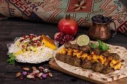 Ein typischens persisches Gericht, mit Reis, Gemüse und Brot sowie Fleischbälcchen in einem Warp drapiert mit Limette und Koriander.