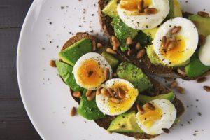 Auf dem Foto erkennt man zwei Scheiben Schwarzbrot auf einem Teller, die mit Avocado und Ei belegt sind. Auf dem Ei sind außerdem noch Pinienkerne drauf verstreut. Die Brote scheinen gewürzt zu sein, denn auf dem weißen Teller erkennt man Pfefferkrümmel