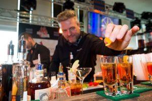 Auf dem Foto ist ein Barkeeper hinter einer Bar zu erkennen, der gerade zweit fertig gemixte rote Getränke mit einem Stück Orange dekoriert.