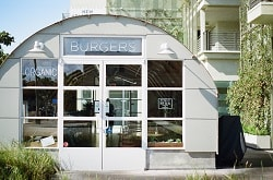 Man erkennt ein Burger Restaurant, welches Bio Burger serviert. Über der Tür steht Burger und links von der Tür das englische Wort für Bio, welches organic heißt. Der Laden sieht aus wie ein Container, man sieht ihn von vorne. Er ist halbrund und grau mit großen Fenstern an der Vorderseite, das heißt da wo sich die Tür befindet.