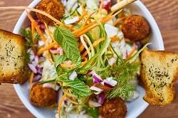 Auf dem Bild erkennt man einen Salat aus der Vogelperspektive. Salatblätter, Karotten und weiteres Gemüse ist zu erkennen. Am Rand des Salats befinden sich Gemüsebällchen, oder auch Falafel genannt.