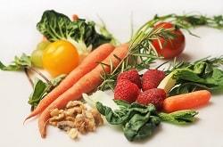 Auf dem weißen hintergrund erkennt man Karotten, Tomaten, Nüsse, Spinat, Salat und Himbeeren verstreut liegen.