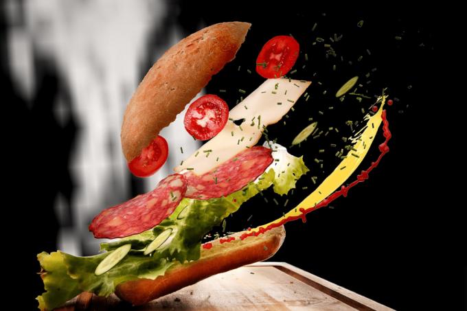 Ein Sandwich was seitlich aus der Luft, auf ein Brett geflogen kommt. Dabei ist es leicht aufgeschichtet. Dei Aufscvhichtung des Snacks ist wie folgt: Brötchen-Unterhälfte, Käse, Salat, Salami, Mozzarella, Tomate, Brötchen-Deckel.
