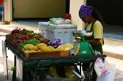 Delasia_Eine Thailändische Frau sitz an Ihrem Ost und Gemüsestand am Straßenrand.