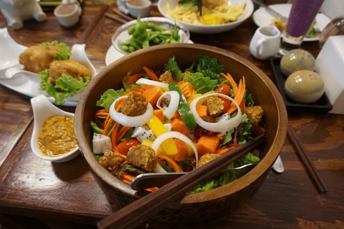 Delasia_Asiatische Gemüse Bowl in einer dunkel braunen Holzschüssel und Essstäbchen serviert auf einem Tisch mit Gemüse und verschiedenen Gewürzen in kleinen weißen Schälchen. Das Gericht enthält Brokkolie, Möhren, Tempeh, Paprika und Zwiebel.