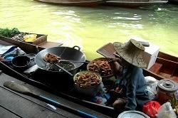 Delasia_Thailändisches Boot im Kanal mit einem Wok ausgestattet in dem ein Einheimischer Essen kocht und es von dort direkt verkauft.