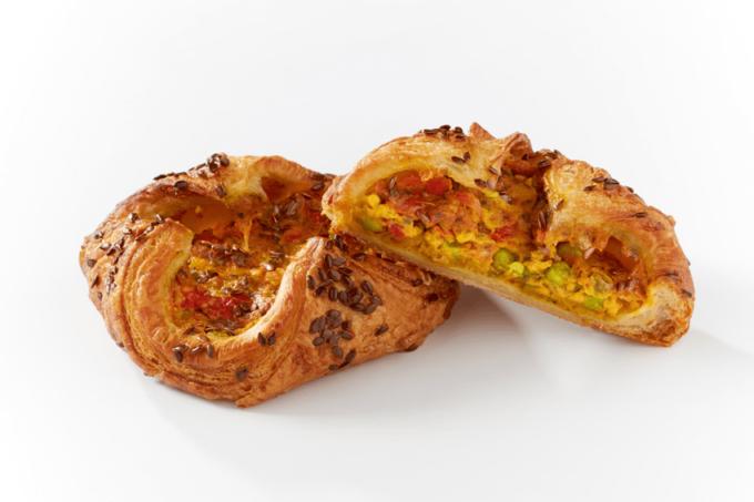 Auf dem Bild erkennt man das Curry-Nest des französischen Herstellers Delifrance. Der Blätterteig-Snack ist von der Seite abgebildet. Eins von zwei Snacks ist in der Mitte durchgeschnitten und auf der andere angelehnt worden, damit der Betrachter des Bilder die Füllung aus Curry, Bohnen und Gemüse des Nestes erkennt. Das Nest ist gold-braun gebacken.