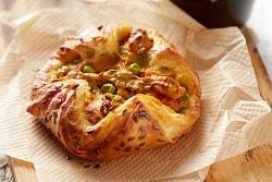 Auf dem Bild erkennt man das Curry-Nest des französischen Herstellers Delifrance. Die Füllung des Blätterteig-Snacks ist inspiriert von indischen Aromen. Der Inhalt ist gelb während das Nest gold-braun gebacken auf einem Einwegpapier liegt.