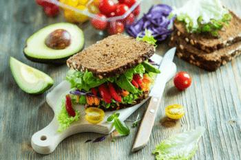 Verschieden Nusse und beeren der Sorte Superfoods sind in Schalen brauner farbe auf einem dunklen Holztisch gestellt. Außerdem stehen im Hintergrund Glaskaraffen mit Frucht- Smoothies. Als deko liegt Salat und Mandarinen mit auf dem Tisch.