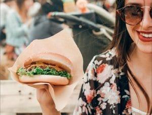 Frischpack: Auf dem Bild ist eine junge Frau mit Sonnenbrille zu sehen die einen urger in der Hand hält, auf dem eine Scheibe Cheddar-Käse geschmoltzen hervorsticht.