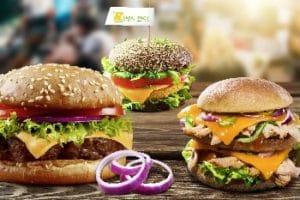 Frischpack: Auf dem Bild sind frei Burger abgebildet, welche mit verschiedenen Cheddar-Sorten belegt sind. Einer von den drei Burgern ist mit veganem Käse Art Cheddar.