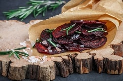 Rote Beete veggie Chips mit Meersalz und frischem Thymian, in einer braunen Tüte auf ein dunkles Holzbrett gelegt.