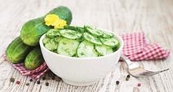 HOMANN Feinkost Gurkensalat mit Homann Salatdressing und Dill zubereitet. Serviert in einer weißen Schüssel.