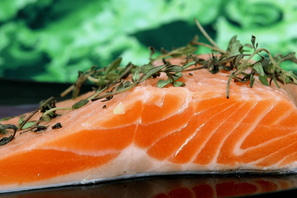 Auf dem Fotot erkennt man ein Stück rosa Lachs. Der Bio-Fisch von Naturland Zeichen liegt auf der Haut, sodass die rosa Seite nach oben zeigt. Auf der farbigen Seite ist der Fisch mit Kräutern garniert. Er liegt auf einem schwarzen Tisch.