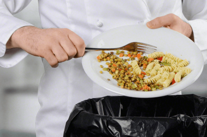 Rauch Verpackung. Lebensmittelverschwendung, auf dem Bild ist ein Koch zu sehen, welcher einen Teller in den Händen hält und das Nudelgericht mit Linsen darauf in den Mülleimer wirft.