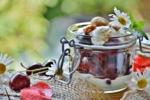 Auf dem Bild ist ein Weck-Glas zu sehen, in dem dem ein Dessert Geschichtet ist. Die untere SSchicht besteht aus einer Joghurt Creme, die zweite aus angedickten Kirschen und die odere wieder aus etwas Joghurt Creme, dekoriert mit Gänseblumen. Das Dessert ist aus einem Tisch drapiert, mit Kaffeesack, Kirschen und Gänseblumen zur Deko.
