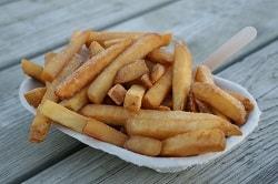 Auf dem Foto ist eine Portion Pommes aus Bio Kartoffeln abgebildet. Es sind dicke, braun gebrannte Pommes, die in einer weißen to go Schale auf einem hellen Holztisch stehen.