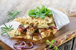 """Nachhaltige veggie Snacks für die gastronomie-auf dem Bild ist ein Panini zu sehen, in weißem Papier eingewickelt und auf ein braunes Holzbrett gelegt. Es liegen Zwiebeln vor dem Panini und Salat oben drauf als Deko. Es ist belegt mit vegetarischen """"Hähnchen""""- Streifen, Salat und geschmolzenem Käse."""