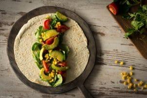 Ein nicht gerollter Wrap belegt mit Avocado, Mais und Tomaten