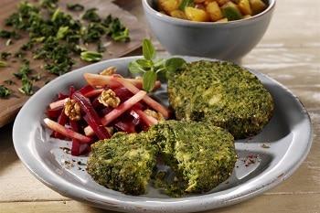 Auf dem Bild ist ein Teller zu sehen, auf dem 2 Burger Patties liegen, die aus Grünkohl-Hanf bestehen. Ebenfalls auf dem Teller befindet sich Gemüse.